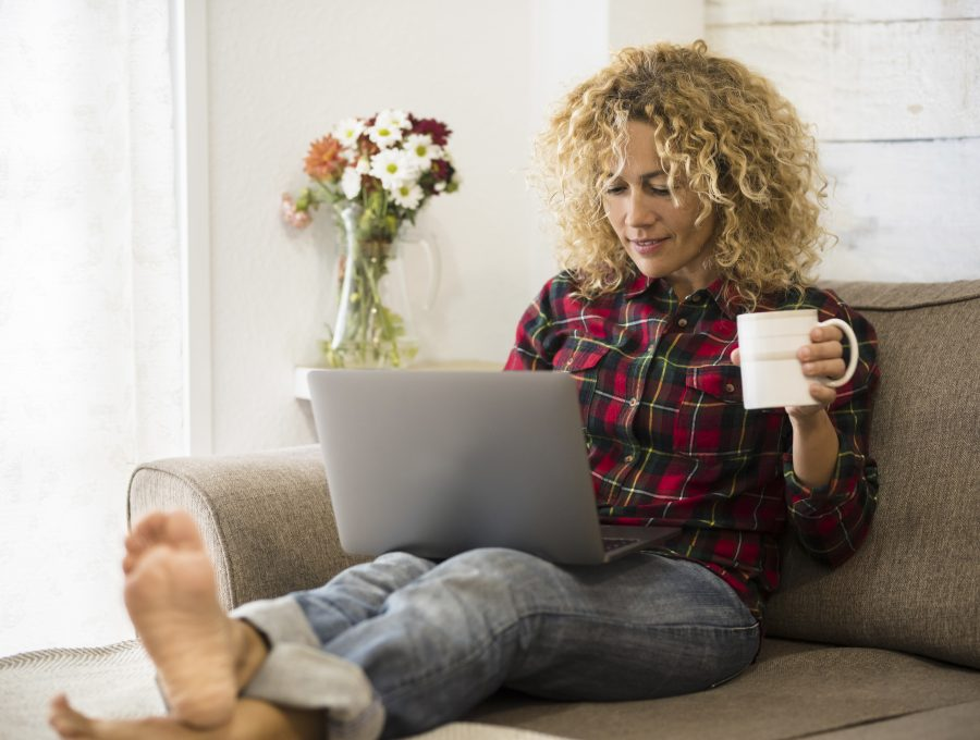 Image of a woman with her feet up on the coffee table, writing on her laptop and drinking tea