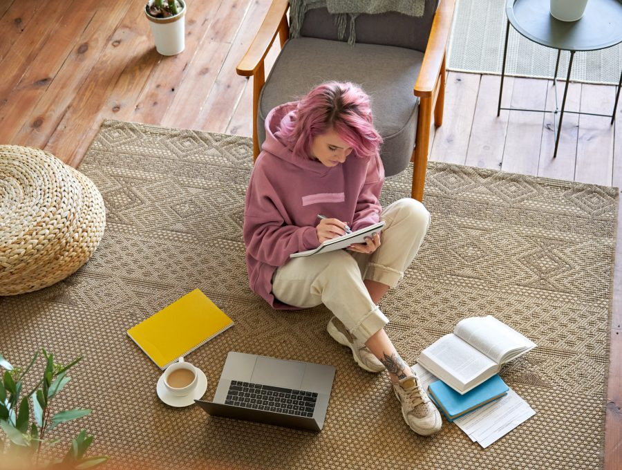 Teen girl studying online on laptop writing notes sit on floor, top view.