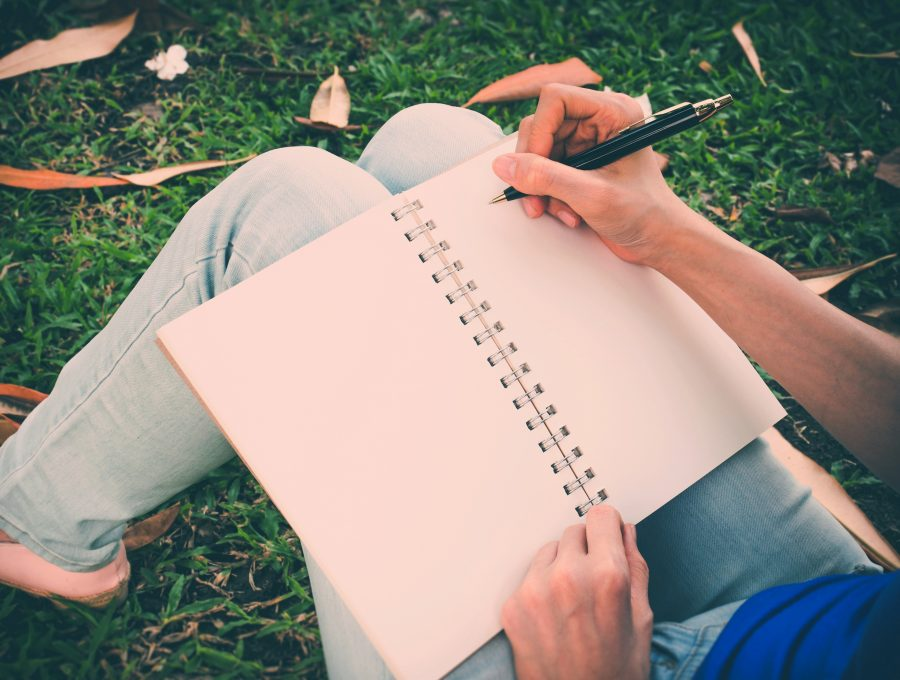 Close-up of someone writing in a notebook in a sunny park