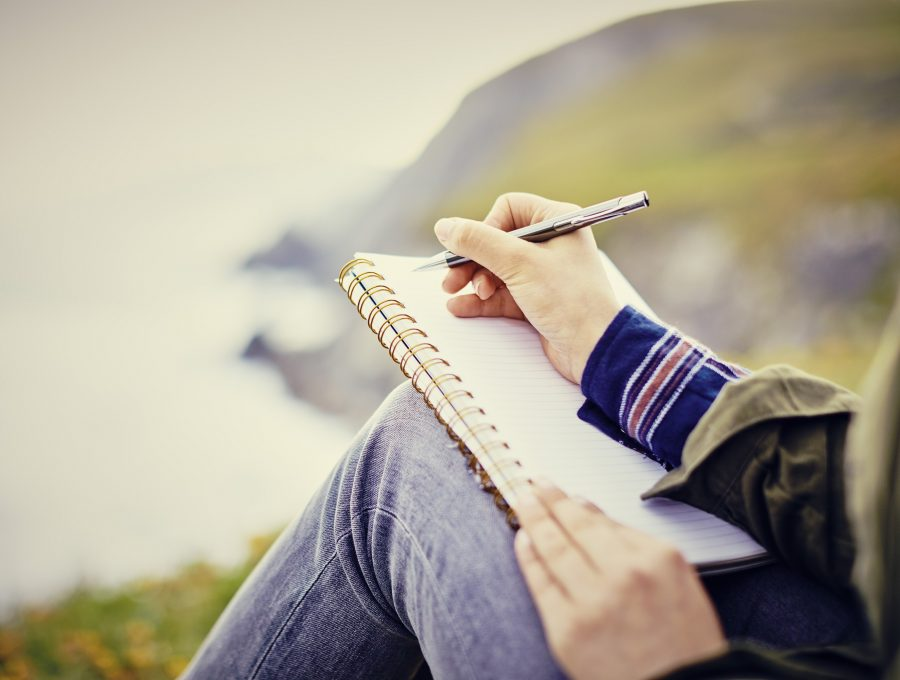 Close-up of a woman writing in a notebook on hillside