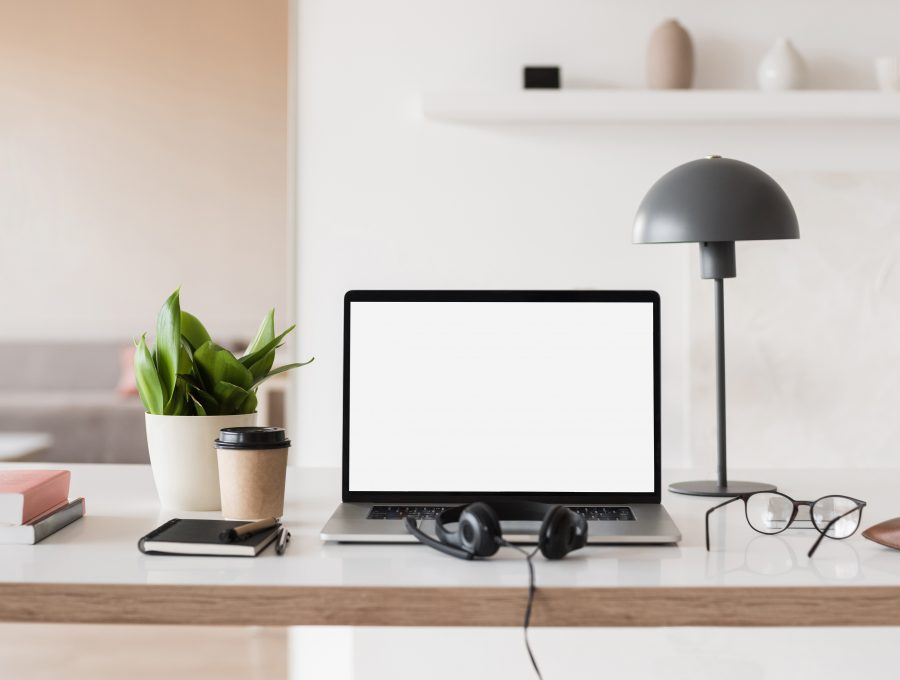 Image of a writing space in a light, modern room, with laptop, headphones, coffee, books and a desk lamp arranged neatly on a table