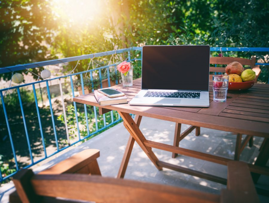 Image of a laptop left on a picnic table on a sunny terrace with blue railings