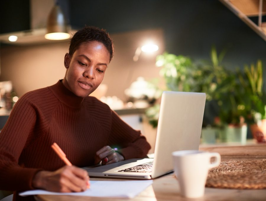 Image of a black woman at large kitchen table, writing notes on a pad of paper with her laptop open in front of her.