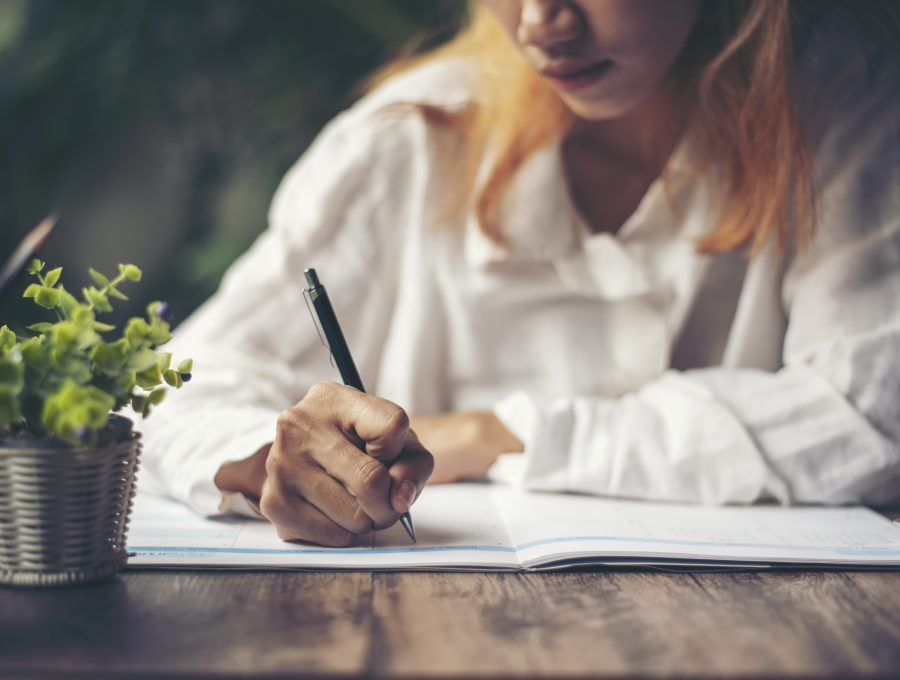 Image of a woman with peach hair and a white shirt writing in her notebook at a table
