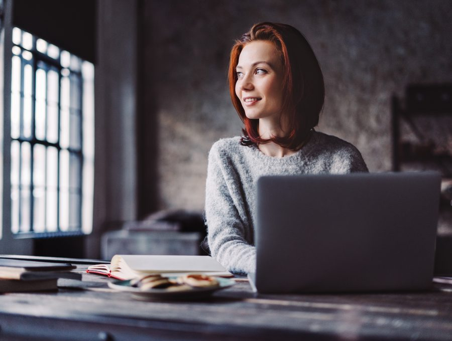 Image of a woman looking out of the window and smiling as she writes on her laptop