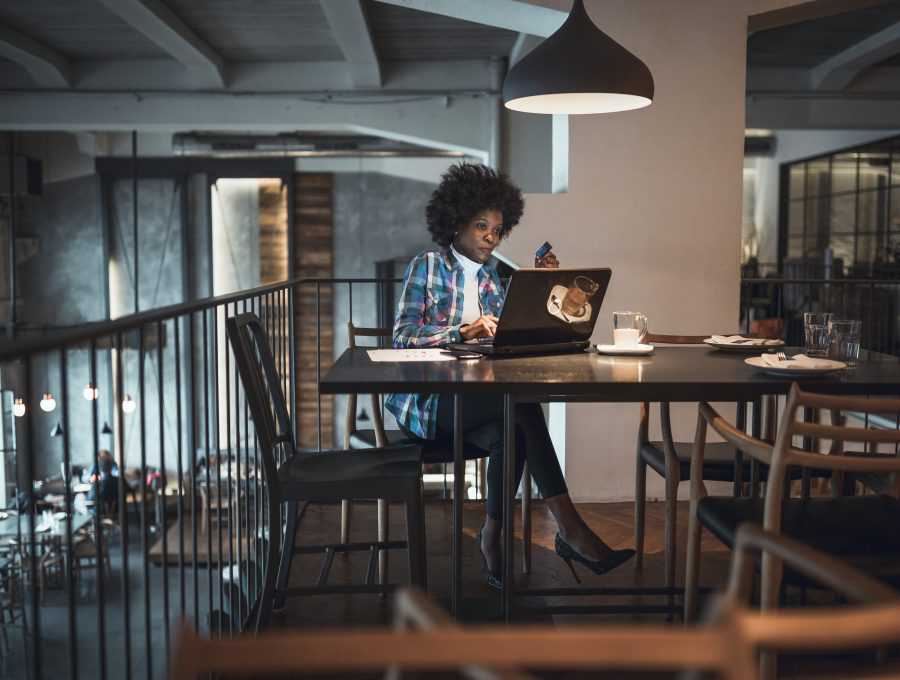 Image of a black woman writing on her laptop at a balcony table in an empty coffee shop