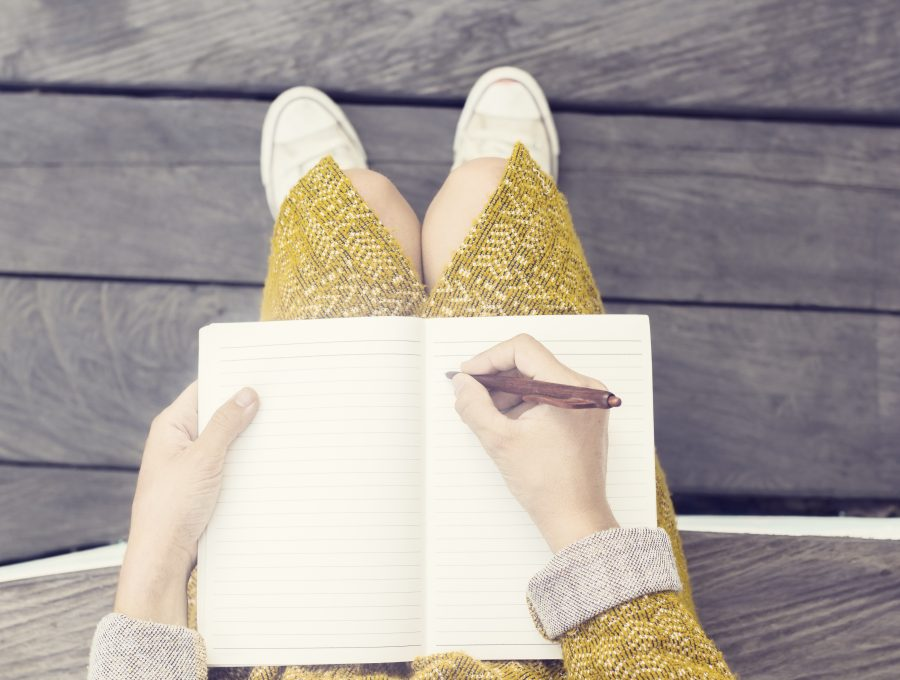Close-up image of a notebook open in a woman's lap, with her pen poised to start writing on a blank page