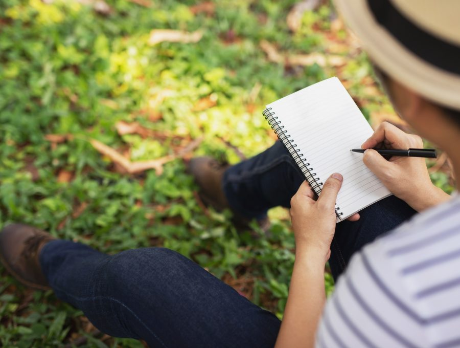 Close up from behind of a man writing in a notebook in a park