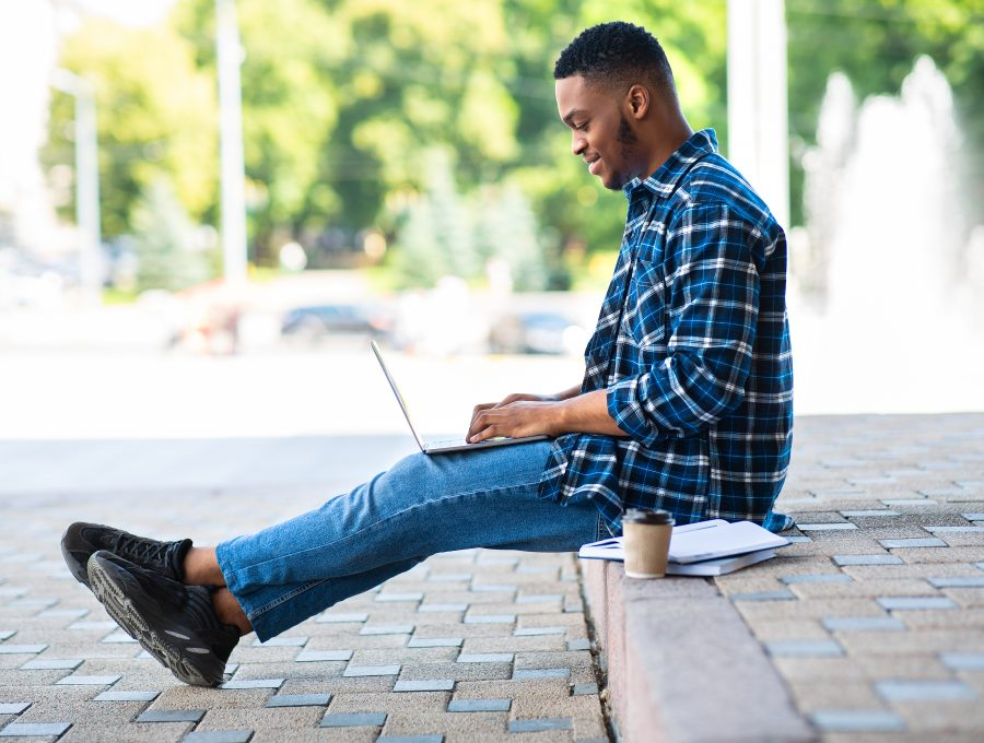 Student using laptop, sitting on the border in city